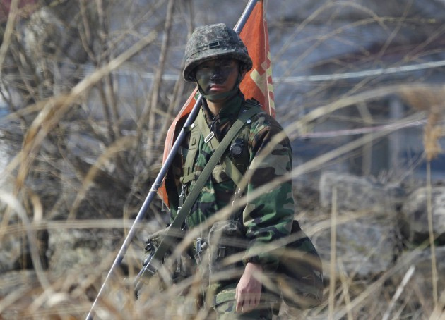 A soldier of a South Korean artillery unit looks at his fellow soldiers and military vehicles moving to conduct military training near the demilitarized zone separating the two Koreas, in Paju